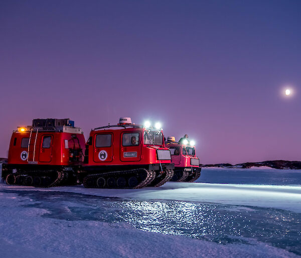 Red and pink Hägglunds vehicles on the sea ice with headlights on and the moon in the distant sky.