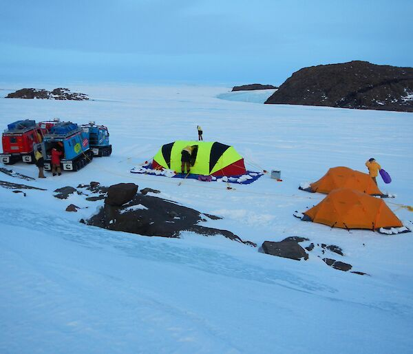 The campground, with the red and blue Hägglunds vehicles parked on the left and fluorescent striped oval shaped Endurance tent is in the middle of the two orange Polar Dome tents on the right.