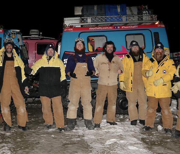 The crew standing along the side of the blue Hagglund vehicle, with big smiles and thumbs up, about to depart in the dark of early morning