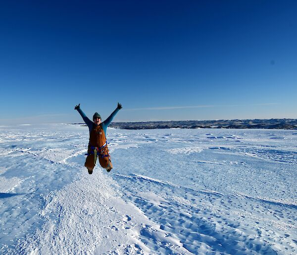 Woman jumping for joy in icy landscape