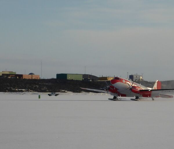 The Basler DC 3 landing on the sea ice with Davis station in the background.