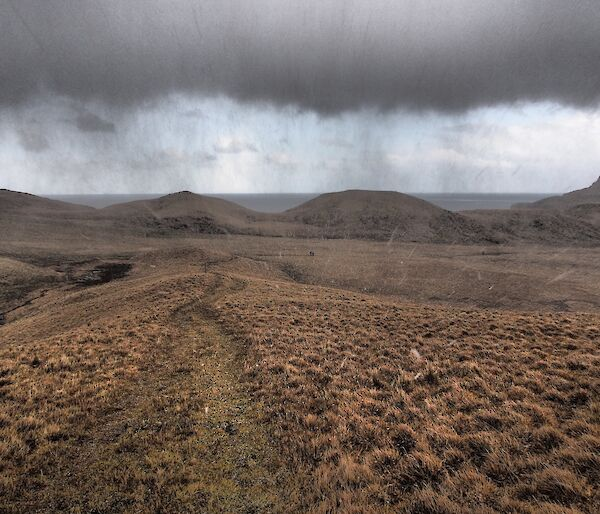Dark clouds and rain begin to drench a plateau on Macquarie Island