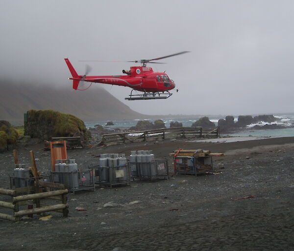 A helicopter lands amongst cargo on a dark and pebble covered beach