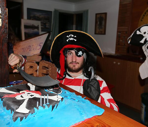 Man in red adn white striped shirt standing behind a birthday cake of a pirate flag
