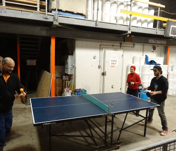 Four people playing table tennis