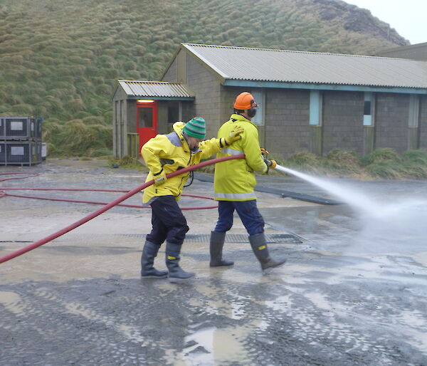 Marion and Nick using a fire hose and spraying water