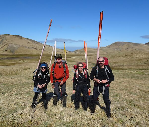 Tasmanian Parks Ranger team standing in a green and brown meadow with orange markers strapped to their backpacks.