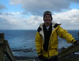 Malcolm standing in a yellow jacket on stairs with ocean in background