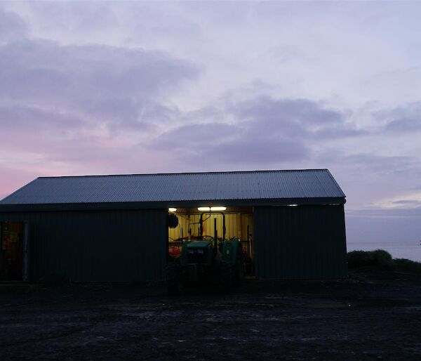A pink sunrise sky over the boat shed with L'Astrolabe in the background