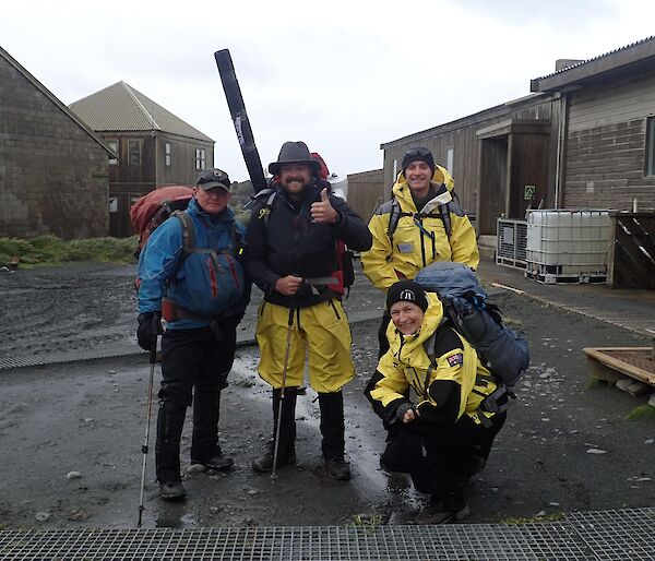 Four people stand in the main square of station kitted out in wet weather clothing and with field packs ready to leave on their familiarisation trip