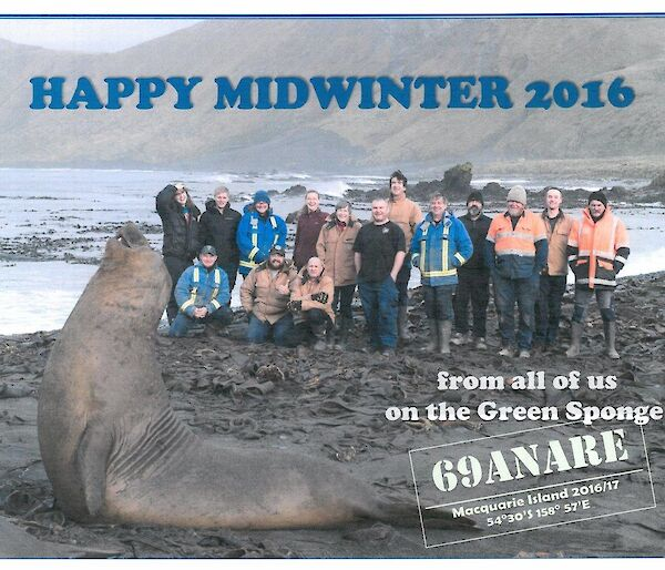 A group photo of the macquarie Island winterers with an elephant seal in foreground