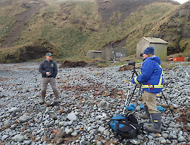 A man being interviewed on the beach with elephant seal in background