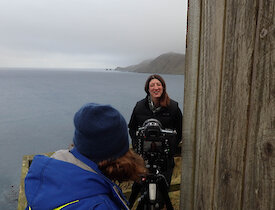 A woman is being interviewed on a balcony above the sea