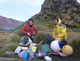 2 men in front of pile of debris they have collected on the beach which includes fishing buoys and lots of plastic