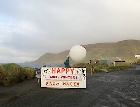 A met balloon is released behibd the Macca noticeboard which states Happy Midwinters