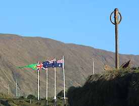 The Australian, New Zealand, Union Jack and ANARE flags flying on a sunny clear (briefly) Midwinter's Day on Macquarie Island