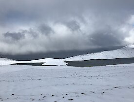 A snowy view on the Varne Plateau with a lake reflecting the grey skies