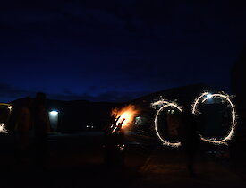 Expeditioners waving sparklers around on Guy Fawkes night near a bonfire in a drum