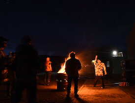 Gathering of expeditioners around a bonfire in a drum for Guy Fawkes night