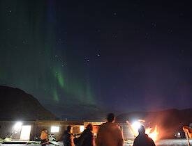 Expeditioners watching the aurora in the sky around a bonfire in a drum