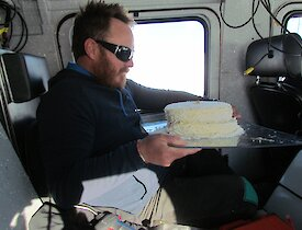 Matt balancing the cake on his knee while driving a vehicle