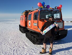 An expeditioner poses in front of a Hägglunds oversnow vehicle which is decorated with balloons