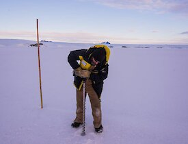 A man drills a hole in the sea ice