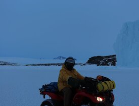 A man on a quad in front of an iceberg.