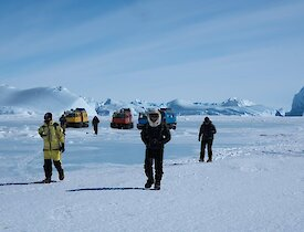A group of people walk away from the vehicles near some icebergs