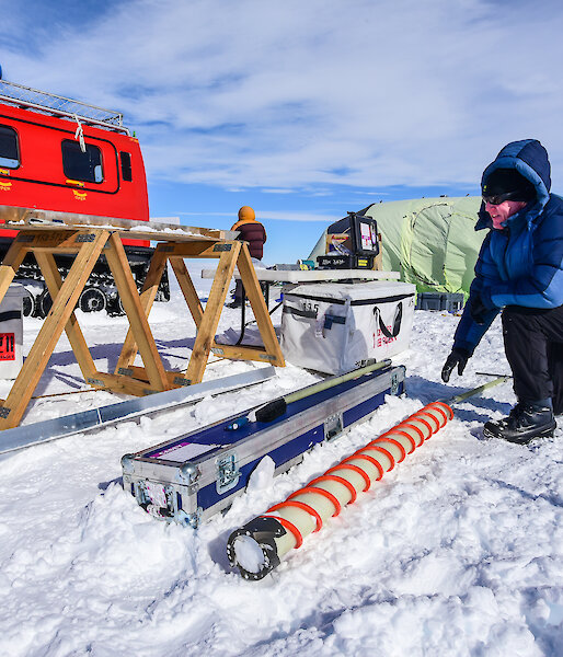 A scientist extracts ice from the ice core drill, with the campsite and Hägglunds in the background.