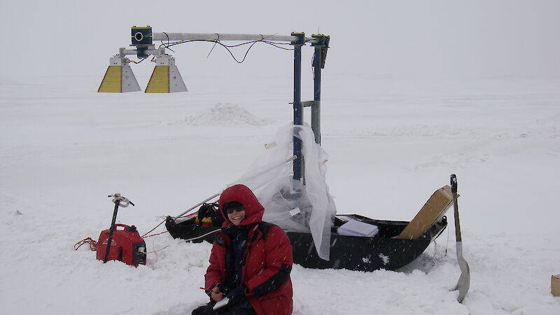 Expeditioner measuring snow thickness on sea ice in front of Davis station using sled-based radar.