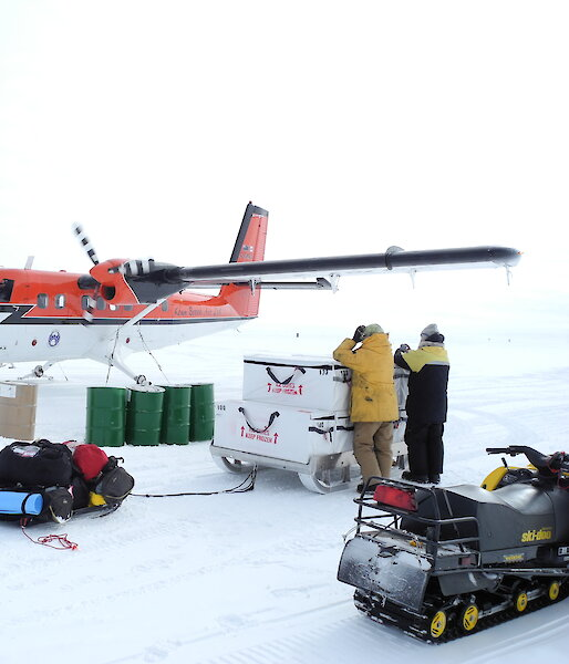 Two expeditioners look at The Twin Otter aircraft. Equipment and a land vehicle are in the foreground