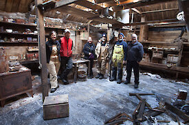 The Mawson's Huts conservation team inside the Main Hut, on completion of the season's work. L-R: Michelle Berry, Marty Passingham, Sally Hildred, Ian Godfrey, Peter Maxwell and David Killick.
