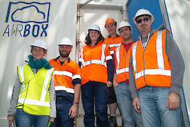 Six members of the AIRBOX team standing outside the shipping container.