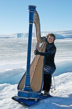 Harpist playing harp on ice with ice cliffs in background