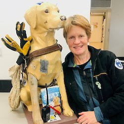 Woman posing with aged fibreglass assistance dog