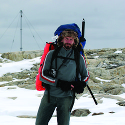 Nick Hutcheson at Wilkes with gear and backpack walking in a snowy landscape