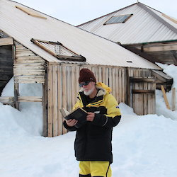 Tom Griffiths stands outside a hut in Antarctica