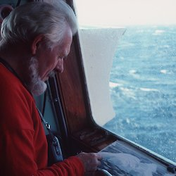 Stephen Walker sketching at a window on board a ship