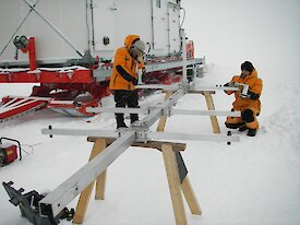 Long metal mast with metals stays in laid out across saw horses in the snow during assembly.