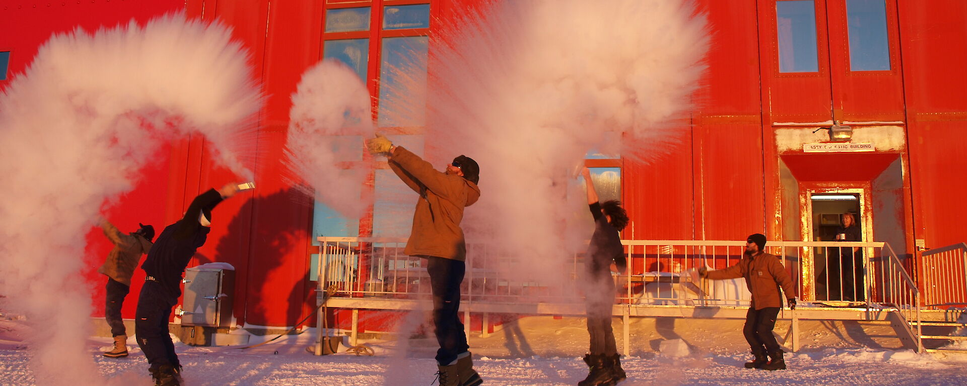 A team of expeditioners throwing boiling water from jugs into the cold air