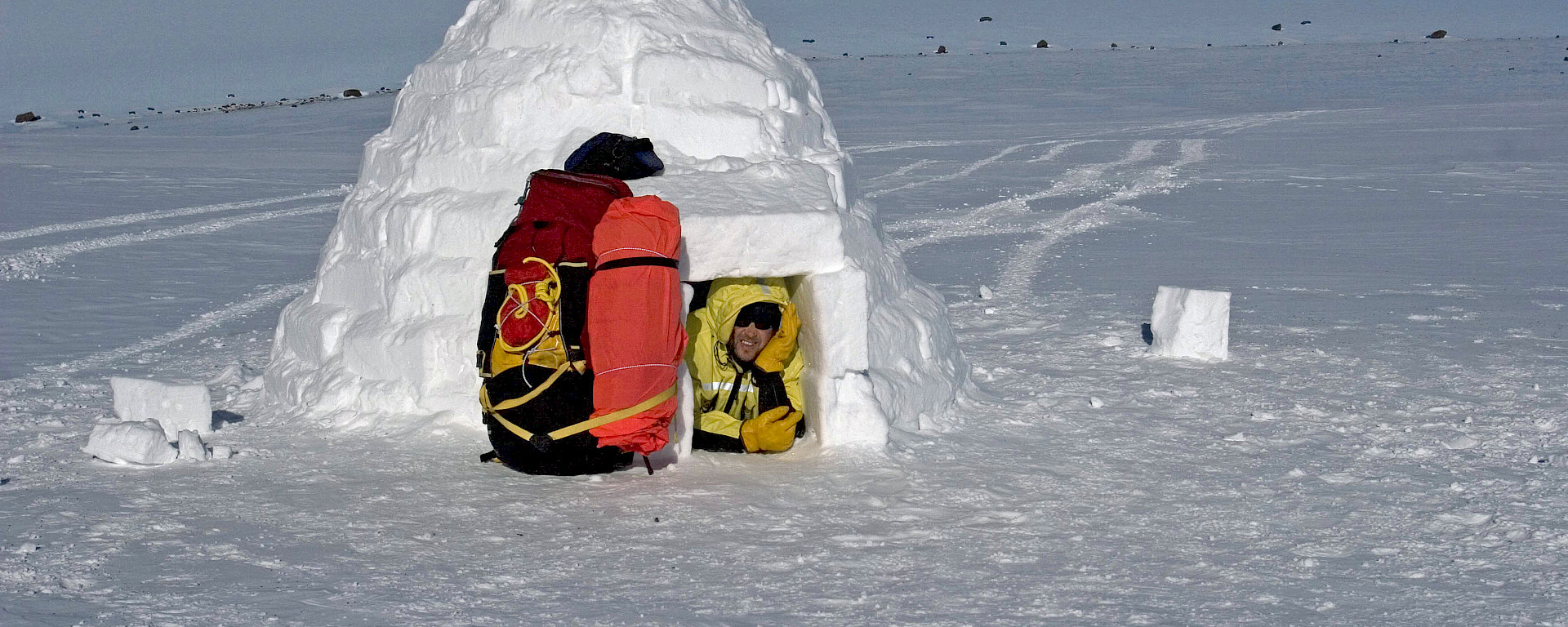 Expeditioner in entry of completed igloo