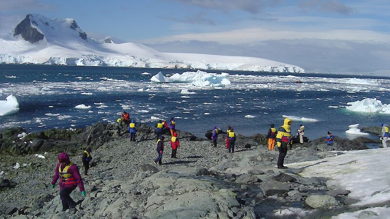 People walking around on the rocky shore with icy mountain in the background