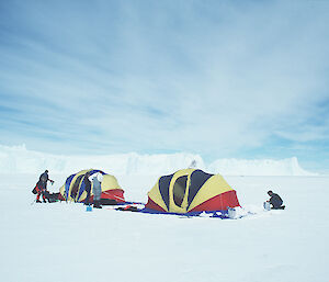 An older image of tourists setting up tents on the ice in Antarctica.