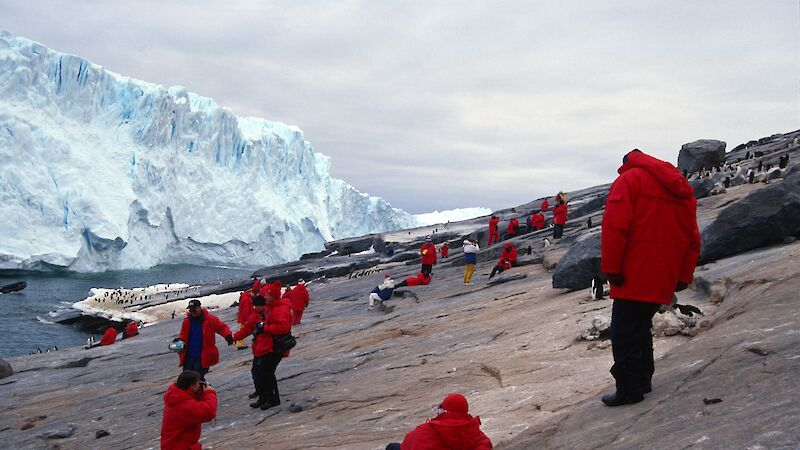 Tourists in various poses are dotted on shore with a glacier in background. Most of them are wearing the same coat.