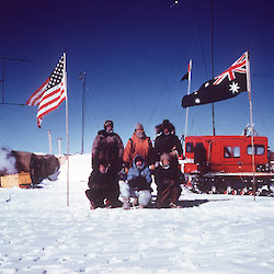 The traverse party stand in front of the vehicle and flags at Vostok