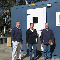 Builders and engineer pose in front of ablutions module