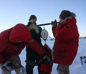 Three expeditioners weighing penguins