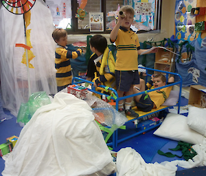 Little boys in a room full or toys, with one child in cot pretending it is a boat.