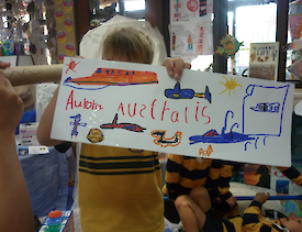 A child holding a cardboard picture of the ship and other little vehicles.